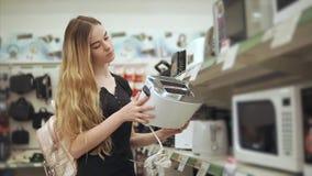 De jonge huisvrouw inspecteert steekproef van broodrooster in een handelzaal van hardware stock footage