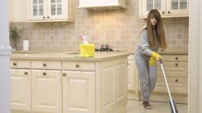 De jonge huisvrouw maakt keukenvloer met zwabber schoon stock videobeelden