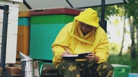 De jonge imkermens schrijft in blocnote controlerend oogst terwijl het zitten dichtbij bijenkorven stock videobeelden