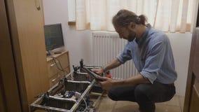 De jonge installatie die van de gpumijnbouw van de technicusvestiging elektrische energieconsumptie meten en gegevens over PC-tab stock videobeelden