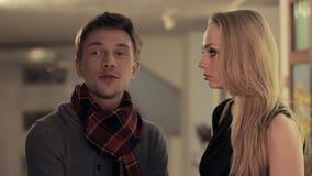 De jonge intelligente kerel komt bespreking aan aantrekkelijke vrouw in kunstgalerie stock footage