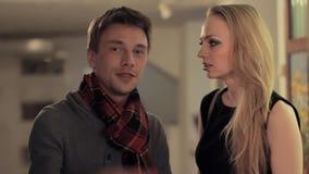De jonge intelligente man komt bespreking aan aantrekkelijke vrouw in kunstgalerie stock footage