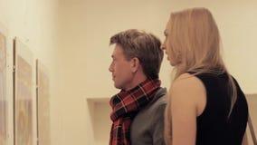 De jonge intelligente man verklaart het schilderen aan aantrekkelijke vrouw in kunstgalerie stock videobeelden