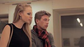 De jonge intelligente man verklaart kunststuk aan aantrekkelijke vrouw in galerij stock videobeelden