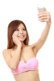De jonge Japanse vrouw in een roze bikini neemt een selfie royalty-vrije stock foto's