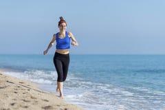 De jonge jogging van de geschiktheidsvrouw bij strand stock foto's