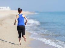 De jonge jogging van de geschiktheidsvrouw bij strand royalty-vrije stock afbeeldingen