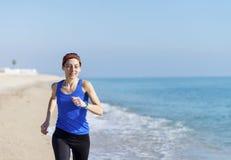 De jonge jogging van de geschiktheidsvrouw bij strand royalty-vrije stock fotografie