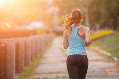 De jonge jogging van de vrouwenagent in park in de ochtend stock afbeeldingen