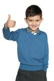 De jonge jongen in blauwe trui houdt zijn duim tegen Stock Afbeeldingen