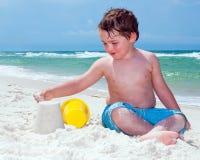 De jonge jongen bouwt zandkasteel Stock Foto's
