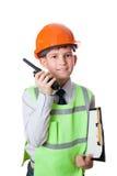 De jonge jongen in bouwvakker en vest spreekt aan draagbare radio Royalty-vrije Stock Foto's