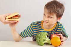 De jonge jongen in een gestreept overhemd bij de lijst weigert hamburger ten gunste van gezonde voeding stock afbeeldingen