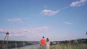De jonge jongen en het meisje houden handen en gaan, tegen de achtergrond van brug, rivier, boom, hemel door stock video