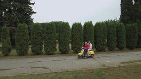 De jonge jongen en het meisje zitten op de autoped in het park Geschoten op Hommel stock video