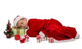 De jonge jongen in feestelijk die Nieuwjaar` s kostuum viel in slaap op doos met gift, op wit wordt geïsoleerd Stock Foto's