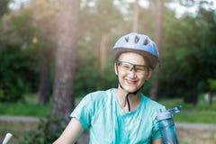 De jonge jongen in helm en groene t-shirtfietser drinkt water van fles in het park Glimlachende leuke Jongen op fiets in het bos royalty-vrije stock foto's
