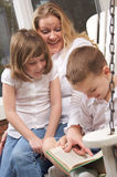 De jonge Jongen leest aan Zijn Moeder en Zuster Stock Fotografie