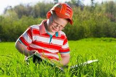 De jonge jongen leest boek in openluchtpark Stock Afbeeldingen