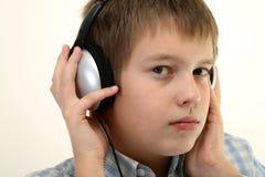 De jonge jongen luistert aan de muziek met hoofdtelefoon stock afbeeldingen