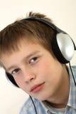 De jonge jongen luistert aan de muziek met hoofdtelefoon Stock Afbeelding
