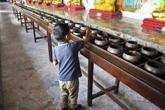 De jonge jongen maakt verdienste door geld bij een Thaise boeddhistische tempel te schenken stock afbeelding