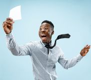 De jonge jongen met een verraste uitdrukking won een weddenschap op blauwe achtergrond stock foto