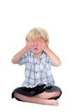 De jonge jongen met van hem overhandigt zijn ogen en witte achtergrond Stock Afbeeldingen