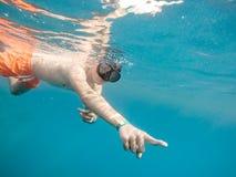 De jonge jongen snorkelt zwemt in koraalrif stock foto's