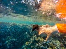De jonge jongen snorkelt zwemt in ondiep water met koraalschool van fis stock foto