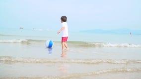 De jonge jongen speelt met kleurrijke waterbal op een mooi zandstrand in Thailand stock footage