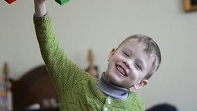 De jonge jongen speelt met zeer gelukkige bouwblokken, stock video