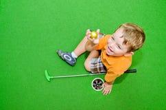 De jonge jongen speelt minigolf Stock Afbeeldingen