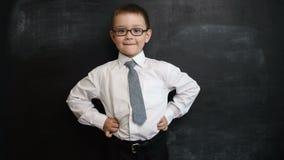 De jonge jongen status in bazig stelt, kijkend recht aan camera Creatief concept van terug naar school en studie Preschool stock footage