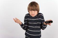 De jonge jongen stelde teleur omdat hij een fundamentele mobiele slechts telefoon heeft Royalty-vrije Stock Afbeelding