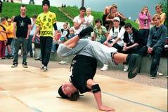 De jonge jongen toont een acrobatische truc. Stock Afbeelding