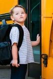 De jonge jongen wacht om bus voor school in te schepen Stock Foto