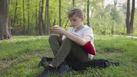 De jonge jongen zit met hoofdkussen in het groene park en het eten van een appel Openlucht recreatie stock footage