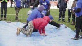 De jonge jongens liggen op blauw geteerd zeildoek, tribune op bevel Emercom opleiding publiek stock footage