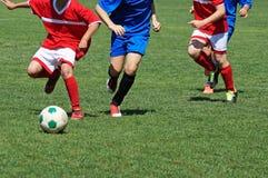 De jonge jongens spelen voetbal stock afbeeldingen