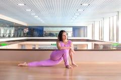 De jonge kalme mooie vrouw die lilac sportkleding dragen die tegen panoramisch venster met pool uitwerken die yoga doen of pilate royalty-vrije stock afbeeldingen