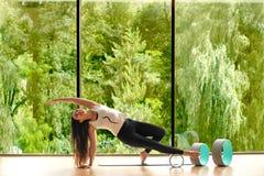 De jonge kalme mooie vrouw die zwarte sportkleding dragen die tegen panoramisch venster met bomen uitwerken die yoga doen of pila royalty-vrije stock foto
