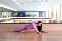 De jonge kalme vrij vrouwelijke dragende lilac sportkleding die tegen panoramisch venster met pool uitwerken die yoga doen of pil stock foto's