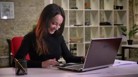 De jonge Kaukasische donkerbruine onderneemster ontvangt bericht op smartphone en krijgt zeer het gelukkige werken in bureau stock videobeelden