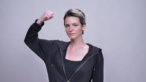 De jonge Kaukasische dunne vrouw toont machtsteken die zich nog op grijze achtergrond bevinden stock videobeelden