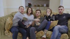 De jonge Kaukasische film van mensenhorloges thuis en eet popcorn stock videobeelden