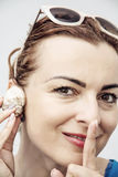 De jonge Kaukasische glamourvrouw luistert zeeschelp en vinger aan haar Royalty-vrije Stock Foto