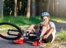 De jonge Kaukasische jongen in helm en witte t-shirt kreeg ongeval en zit op de grond na het vallen van de fiets en voelt pijn royalty-vrije stock afbeelding