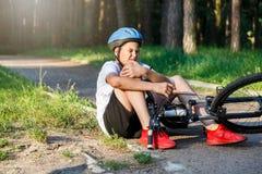De jonge Kaukasische jongen in helm en witte t-shirt kreeg ongeval en zit op de grond na het vallen van de fiets en voelt pijn stock foto