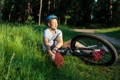De jonge Kaukasische jongen in helm en witte t-shirt kreeg ongeval en zit op de grond na het vallen van de fiets en voelt pijn royalty-vrije stock foto